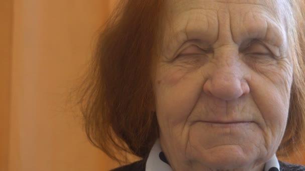 portréja egy mosolygó idős nő néz a kamerába