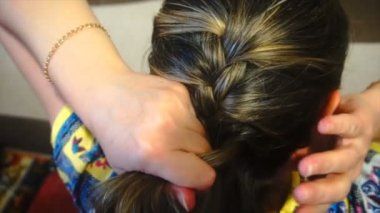 woman braids pigtails herself, slow motion