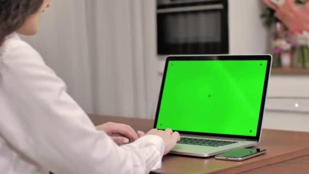 Žena používající notebook se zelenou obrazovkou, 4k záběr. Technologie, chroma klíč, šablona, mockup a koncepce zábavy.