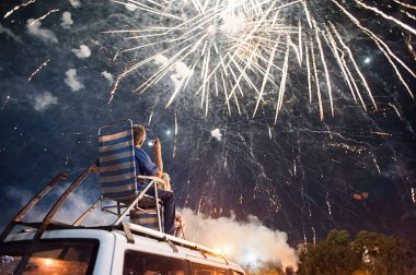 Man watching fireworks and sits in comfortable garden chair on car roof
