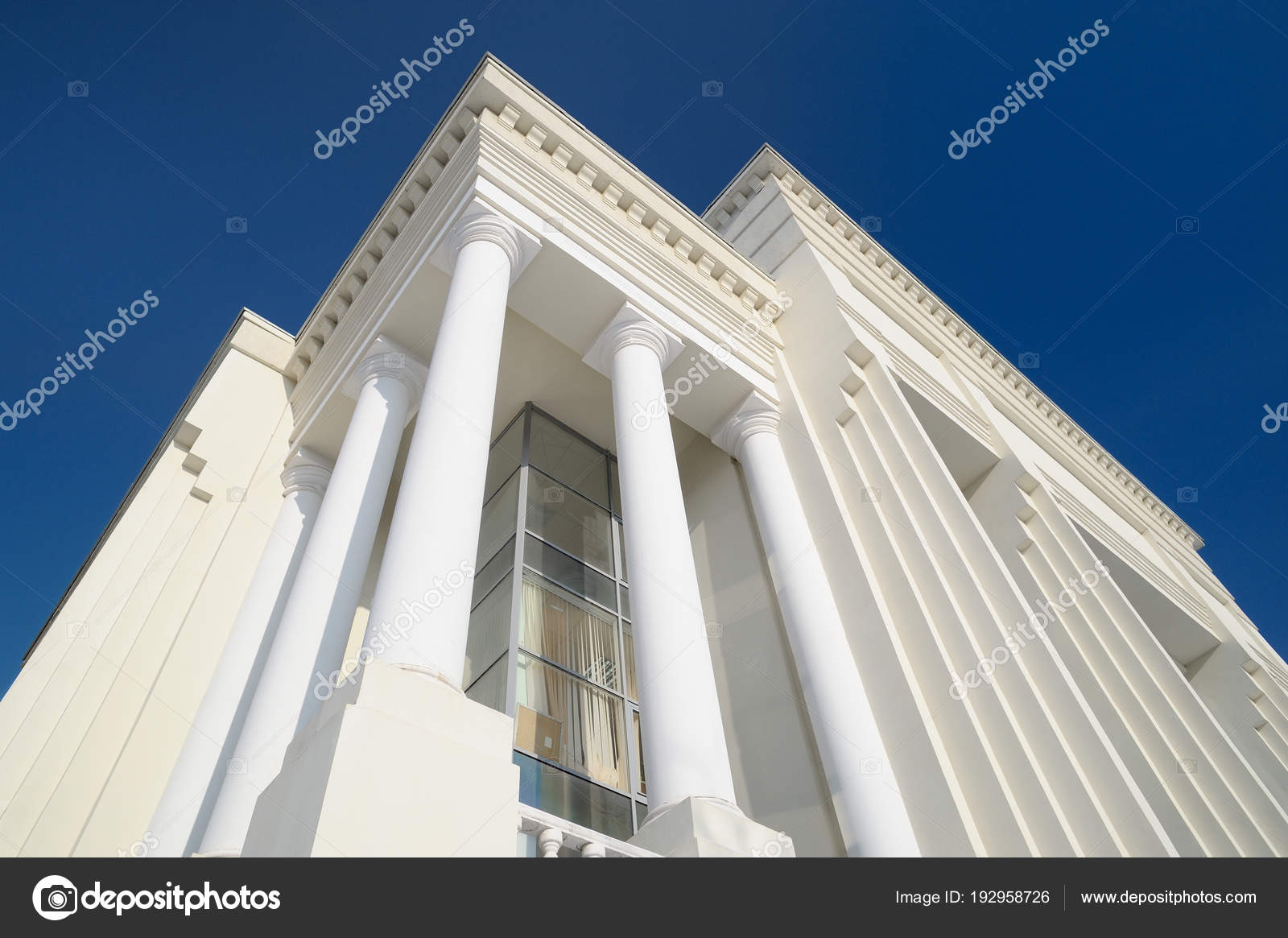Classic style white building facade detail with pillars against clear blue sky modern architecture stock image