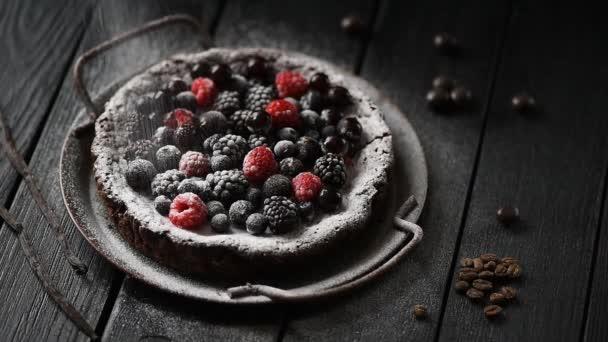 Domácí pečení. Švédský čokoládový dort kladdkaka s malinami, rybízy a borůvky v prášku s třešňovým cukrem na černém pozadí nízký klíč