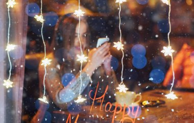 Young beautiful woman sitting in cafe, drinking coffee. Model listening to music. Magic snowfall effect. Christmas, Happy new year, Valentines day, winter holidays concept. The photo was taken through the window