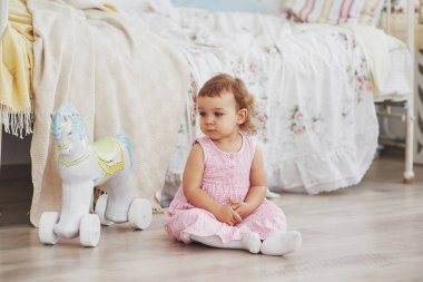 Baby girl in cute dress siting at bed playing with toys by the home. White vintage childroom. Childhood concept.