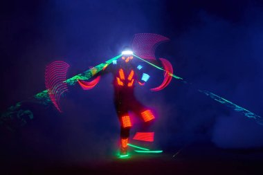 Laser show performance, dancers in led suits with LED lamp, very beautiful night club performance, party.