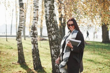 Cheerful look. Young smiling brunette in sunglasses stands in the park near the trees and holds notepad.