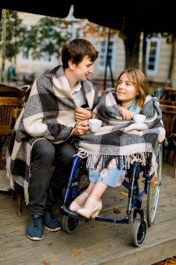 Attractive young woman on a wheelchair drinking coffee in a cafe outdoors with her husband and having a good time. Couple in wheelchair covered with checkered plaids outdoors