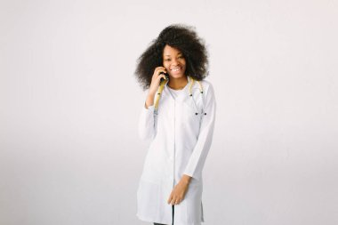 Female doctor Preparation medical equipment. An African American female medical doctor with a stethoscope in hospital on white background and talking on the phone