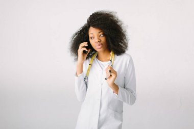Portrait of a young african doctor in uniform with a stethoscope in hospital on white background and talking on the phone