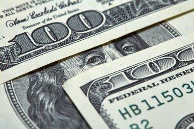 Benjamin Franklin's eyes between two hundred dollar banknotes close-up