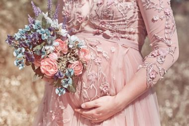 Pregnancy, people and maternity concept - pregnant woman belly closeup in a beautiful lace glamour dress with flowers. Mom Expecting Baby.