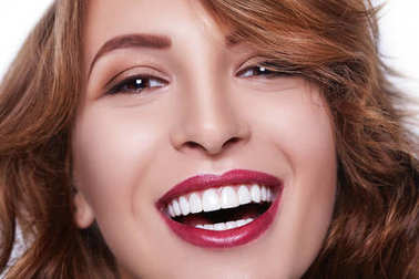 Healthy white smile close up. Beauty woman with perfect smile, lips and teeth. Beautiful Model Girl with red lips isolated on white background. with perfect skin. Teeth whitening.