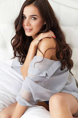 Portrait of a happy young beautiful brunette women in the morning. Gorgeous model with perfect long hair smiling in bed.