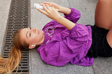 Close up portrait of young fitness blonde woman in sportswear using mobile phone after fitness workout outdoors at beautiful sunny day.