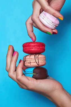 Woman hands with colourful manicure holding colourful macaroons. Blue background
