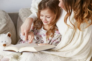 Happy Mother and daughter sitting on bed under plaid and reading book. Maternity concept. Parenthood. Motherhood