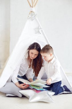 Mother playing with her son in a teepee. Maternity concept. Parenthood. Motherhood