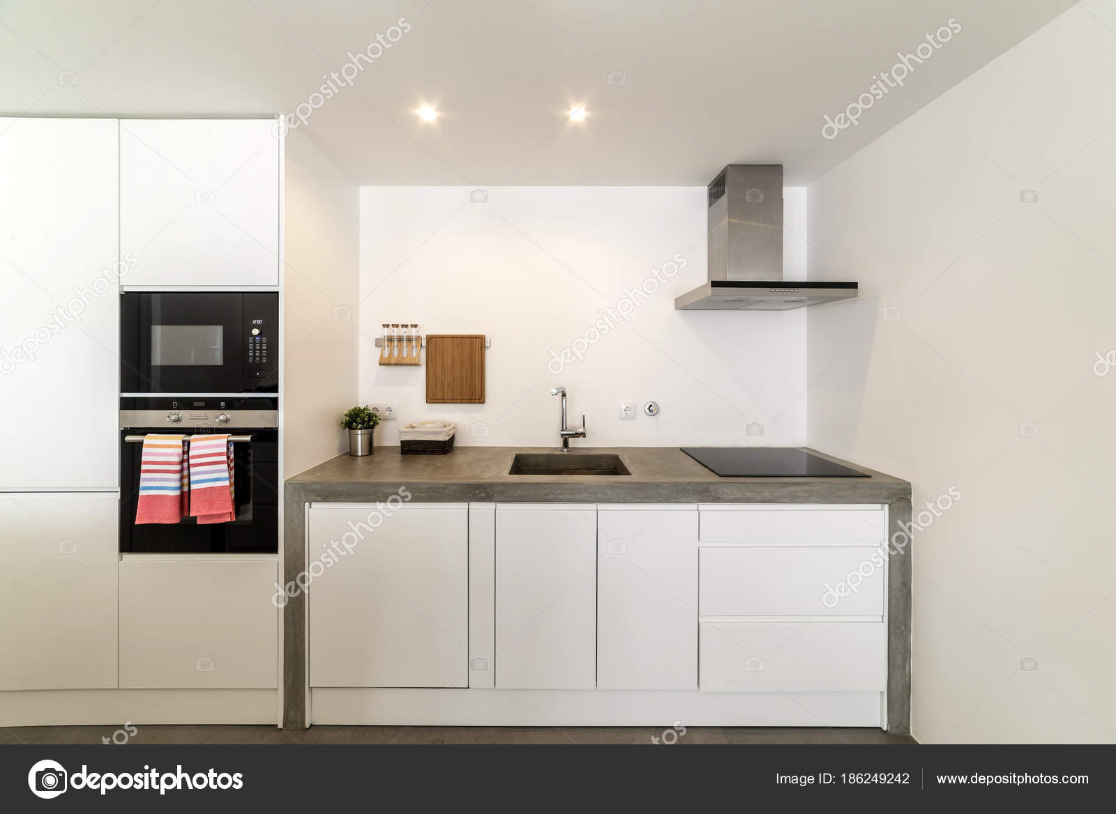 Cucina moderna con pavimento di piastrelle grigie e muro bianco