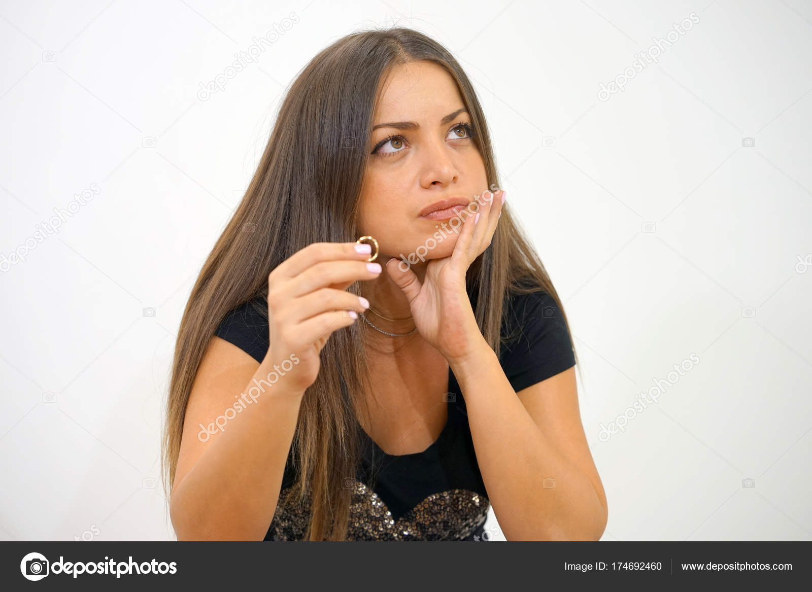 A girl holding a wedding ring doubtfully — Stock Photo © svershinsky