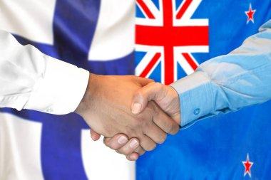 Handshake on Finland and New Zealand flag background.
