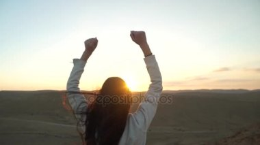 Young woman lift her arms up in a desert scenery