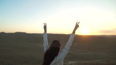 Girl with her arms up in victory during a desert sunset - goal reach