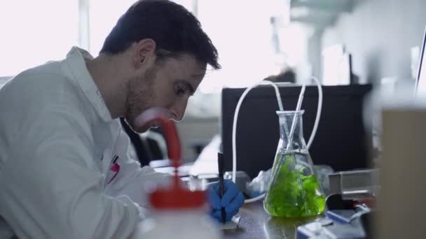 A tudós a laborban jegyzeteket ír le, miközben az algás lombikot nézi.
