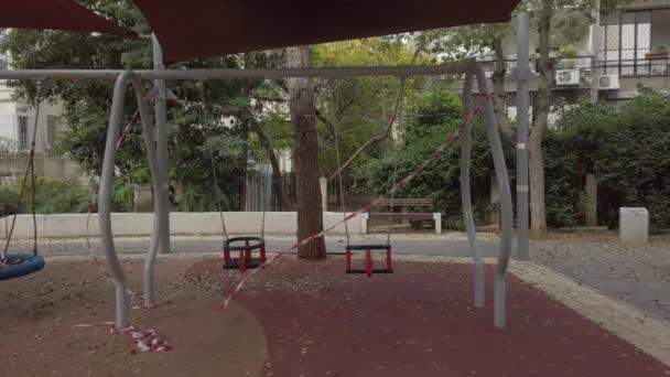 Hinták egy üres játszótéren, piros-fehér szalaggal lezárva.