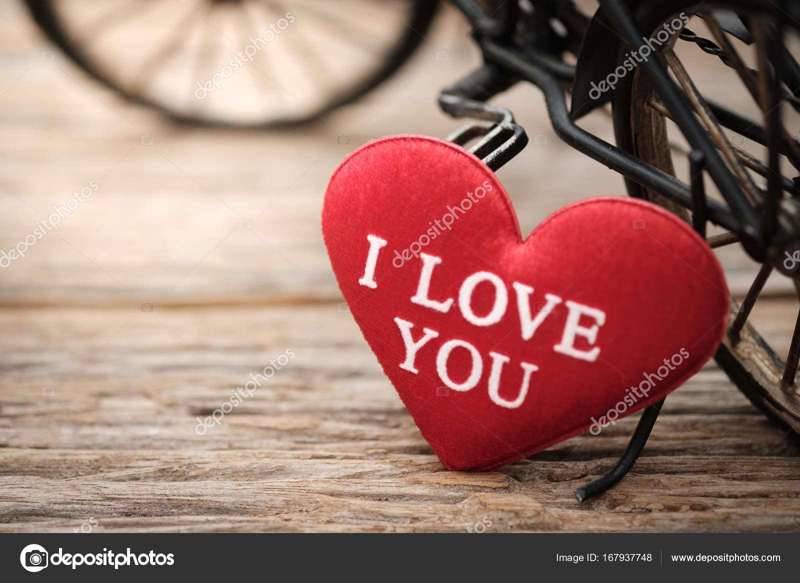 3944cced9e5a2 Forma de corazón rojo almohada y bicicleta de juguete en madera fondo con  espacio para escribir. Concepto de San Valentín