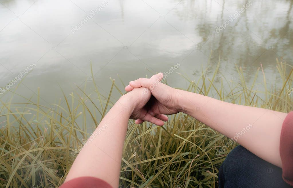 A woman holding her hands on the river.