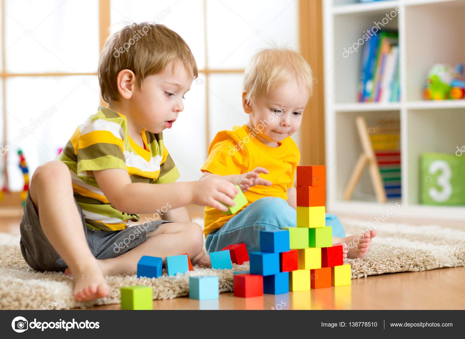 chicos de nios nios pequeos y nios en edad preescolar juegan con bloques de juguete en casa o guardera u foto de oksun