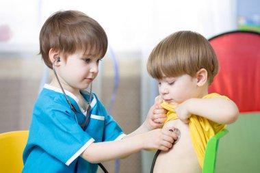 Children playing doctor in playroom or kindergarten