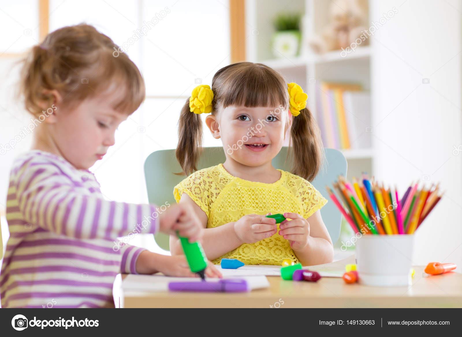 sonriendo a los niños pintando en su casa o centro de cuidado diurno ...