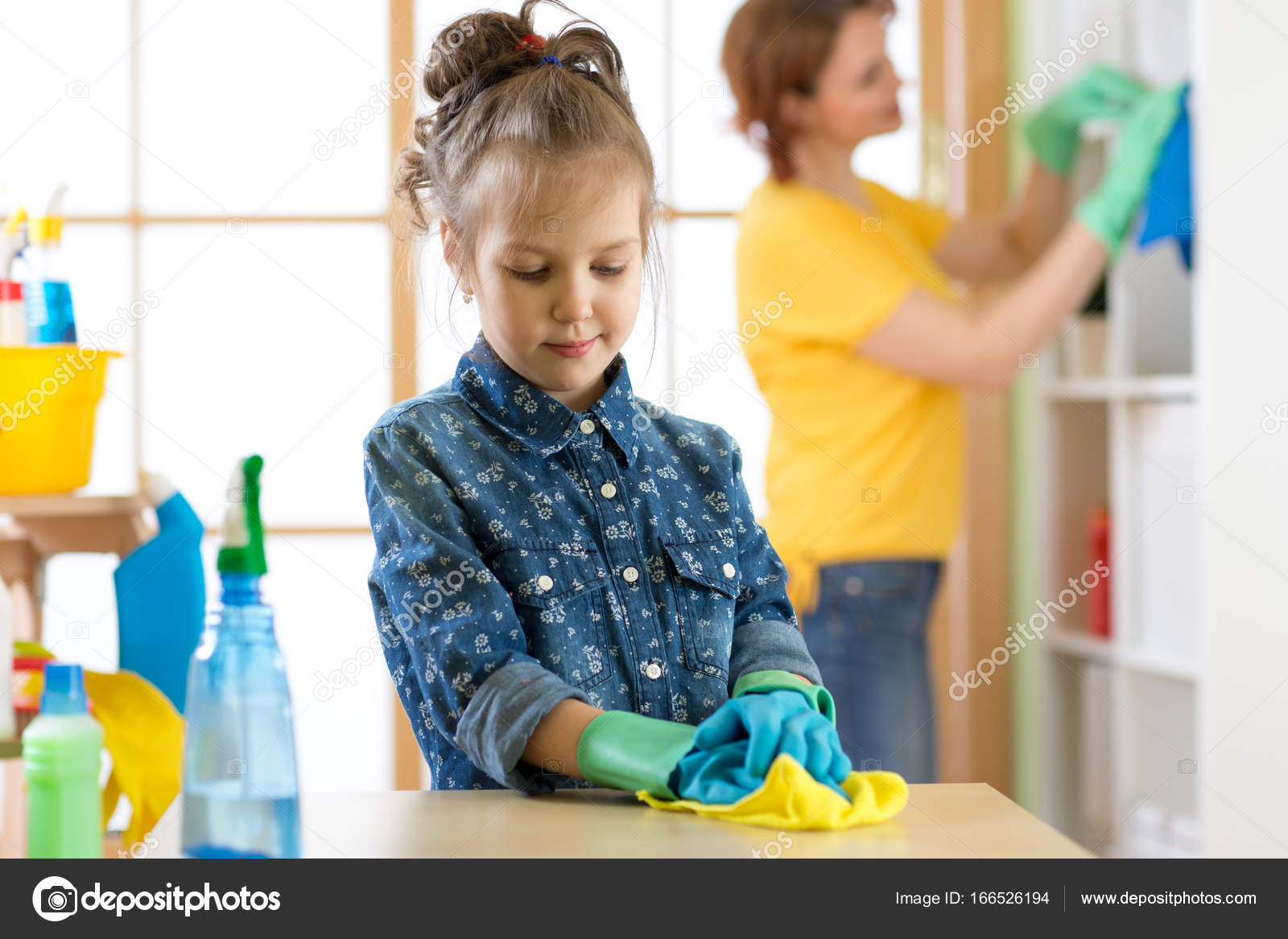 Jongen meisje en moeder maken schoonmaken kamer thuis u stockfoto
