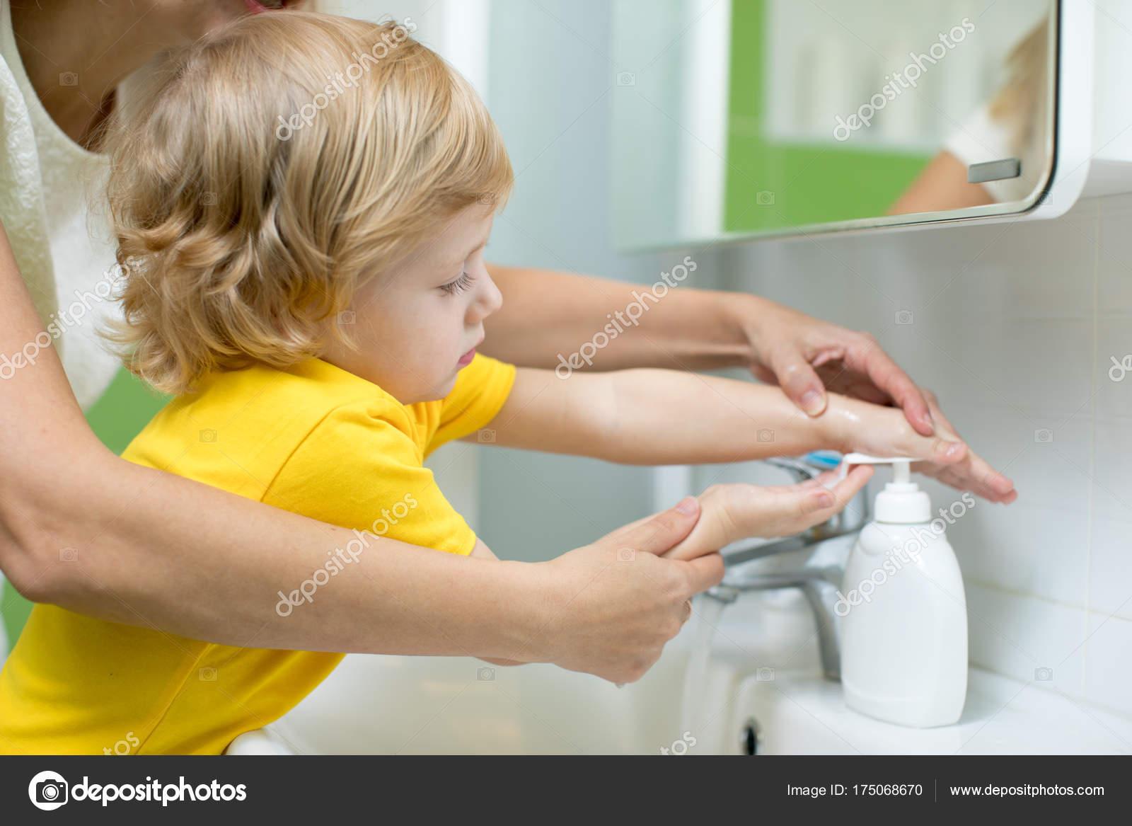 Mutter und Kind Sohn waschen ihre Hände in das Badezimmer. Sorge für ...