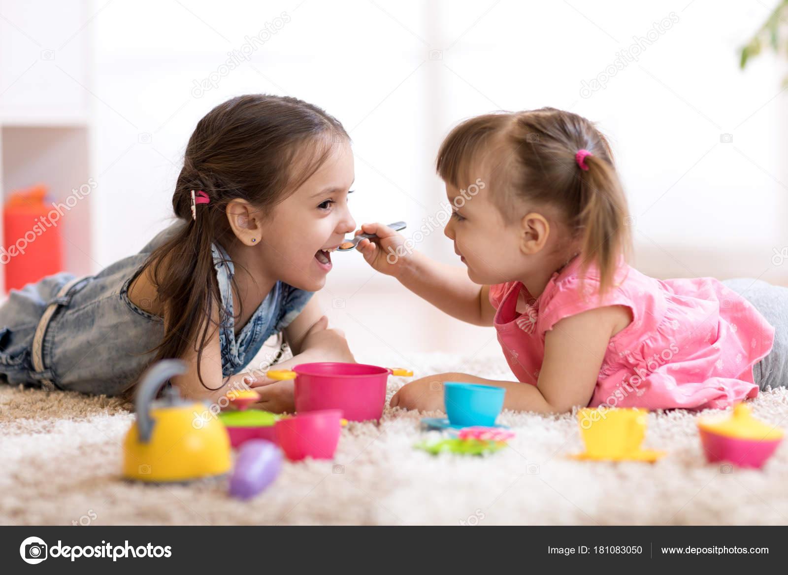 Lindos niños pequeños jugando con utensilios de cocina mientras se ...