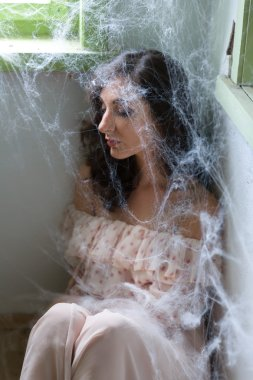 Woman in corner with cobwebs