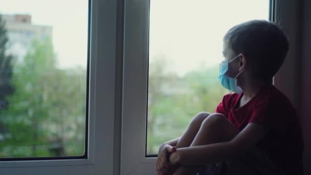 Smutný chlapec v lékařské masce sedí na parapetu a dívá se z okna, v karanténě. Pohled z ulice. Pacient izolován, aby se zabránilo infekci koronaviru, Covid-19 epidemie, pandemie. Zůstaň doma.
