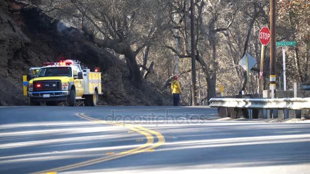 Požární posádky monitory a chrání dojíždějících z ohně / hasič posádky a truck jsou na místě ochrana svahu na ohni v Ojai v Kalifornii