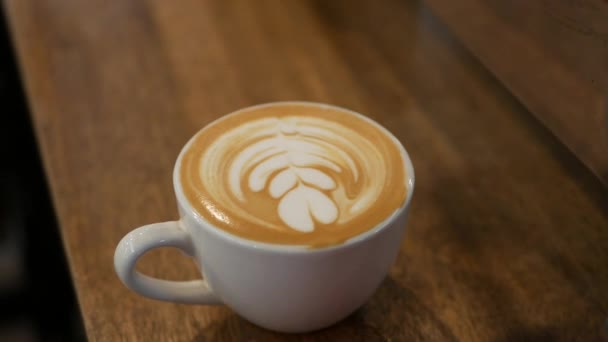 Cup of coffee with latte art. Barista made a beautiful art on milk foam. Close-up