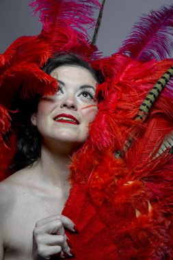 Burlesque girl with red bird feathers and pheasant