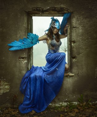 Beautiful young woman with dress made of blue feathers, angel fa