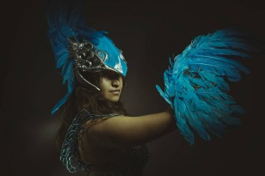 Beautiful latin woman in blue feather bird costume