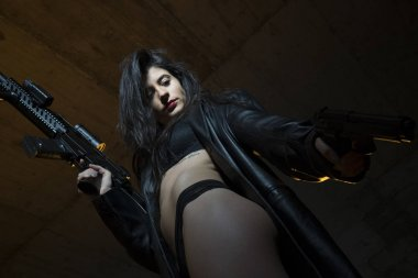 Army brunette girl with gun in a garage