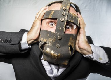 Businessman with iron mask on face
