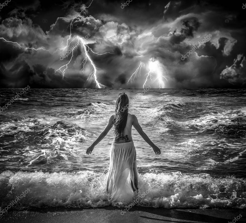 Brunette girl with bare chest looking back to the storm next to the mediterranean sea in Barcelona, Spain