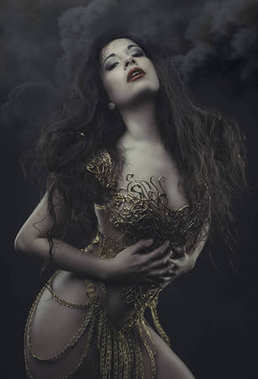 fashion brunette woman dressed in goth style with a dress of golden threads and mask with skull