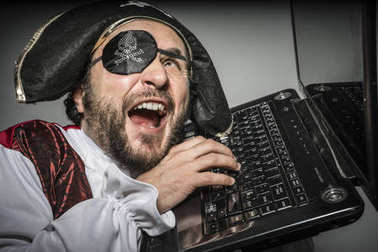 Man in pirate clothes, attempt to hack a laptop