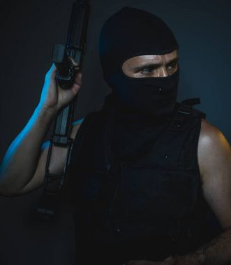 hit man, armed and dangerous man with balaclava and bulletproof vest, concept killer contract