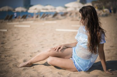 relaxed girl in the sand on the beach by the sea in summer. He wears short jeans and a light blue T-shirt